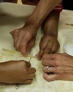 Brown and white hands sewing a Sefer Torah